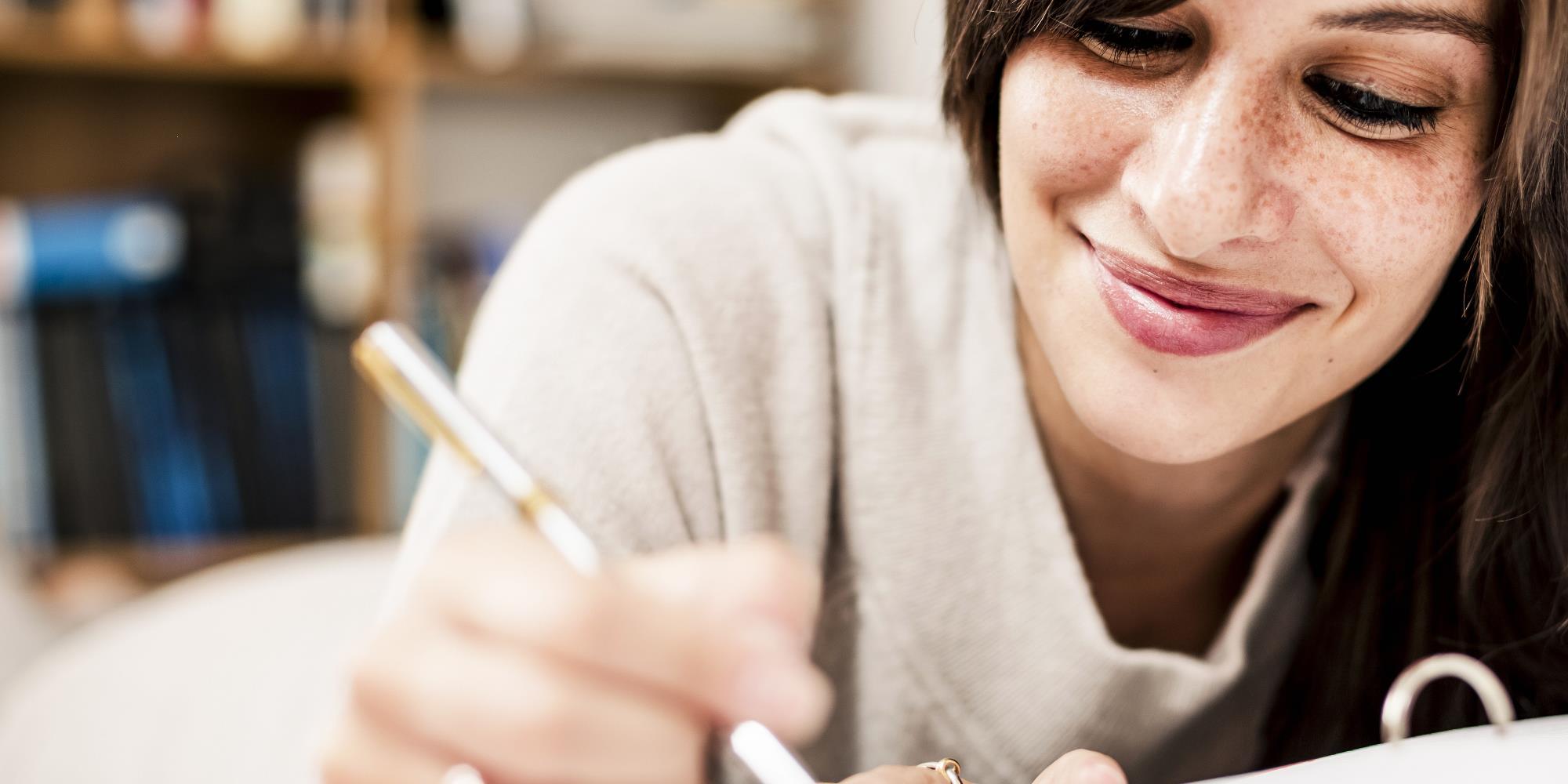 Eine junge Frau schreibt in ein Ringbuch und schaut zuversichtlich ihrer Prüfung entgegen.